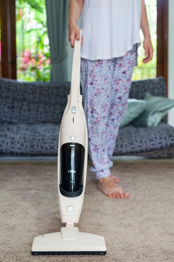 Νέα γυναίκα που χρησιμοποιεί μια ηλεκτρική σκούπα καθαρίζοντας τον τάπητα στο σπίτι στοκ εικόνες