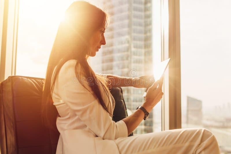 Νέα γυναίκα που χρησιμοποιεί τη συνεδρίαση PC ταμπλετών στην πολυθρόνα κοντά στο παράθυρο με την άποψη πόλεων στοκ εικόνες