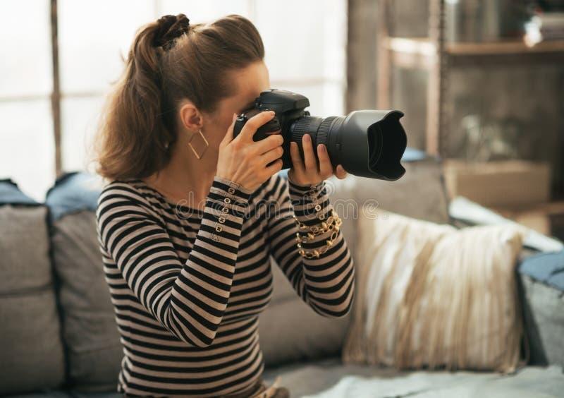 Νέα γυναίκα που χρησιμοποιεί τη σύγχρονη κάμερα φωτογραφιών dslr στοκ φωτογραφία