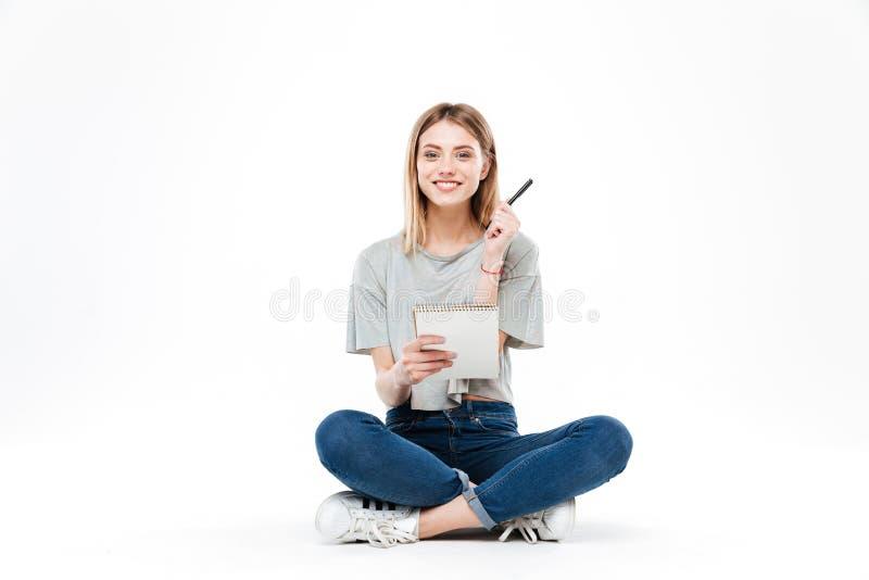 Νέα γυναίκα που χρησιμοποιεί το μολύβι και το σημειωματάριο στοκ εικόνες με δικαίωμα ελεύθερης χρήσης