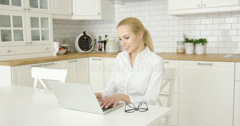 Νέα γυναίκα που χρησιμοποιεί το lap-top στην κουζίνα στοκ φωτογραφία με δικαίωμα ελεύθερης χρήσης