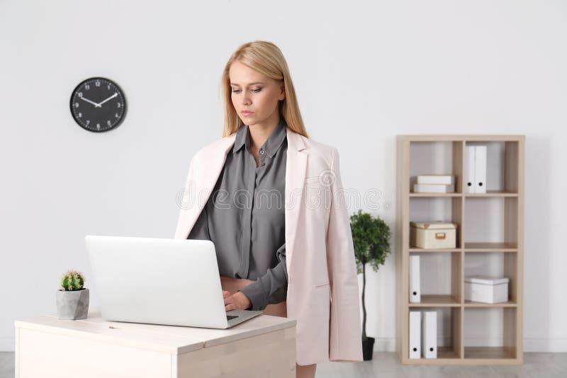 Νέα γυναίκα που χρησιμοποιεί το lap-top στη στάση επάνω στον εργασιακό χώρο στοκ φωτογραφία με δικαίωμα ελεύθερης χρήσης