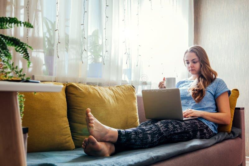 Νέα γυναίκα που χρησιμοποιεί το lap-top της στο καθιστικό στοκ εικόνα