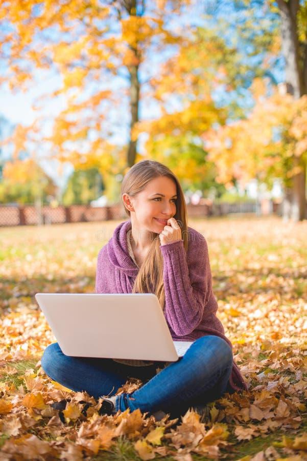 Νέα γυναίκα που χρησιμοποιεί το lap-top της υπαίθρια το φθινόπωρο στοκ φωτογραφία