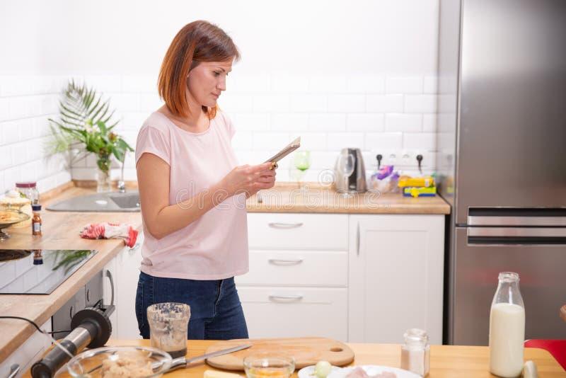 Νέα γυναίκα που χρησιμοποιεί το smartphone που κλίνει στην κουζίνα σε ένα σύγχρονο σπίτι τηλεφωνικό μήνυμα ανάγνωσης γυναικών red στοκ φωτογραφία