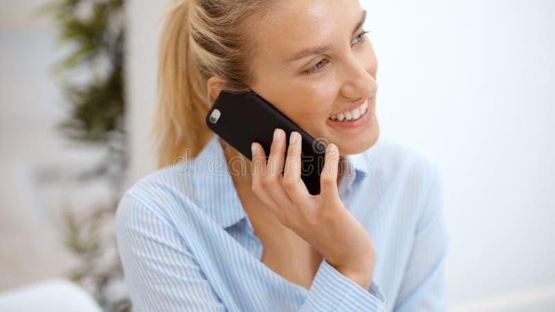 Νέα γυναίκα που χρησιμοποιεί το smartphone στο σπίτι στοκ εικόνα