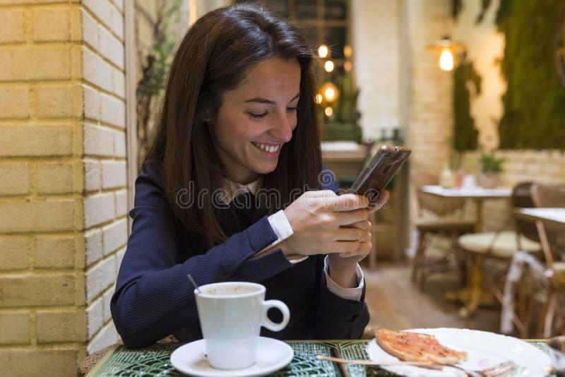 Νέα γυναίκα που χρησιμοποιεί το smartphone στο breakgast στοκ εικόνες