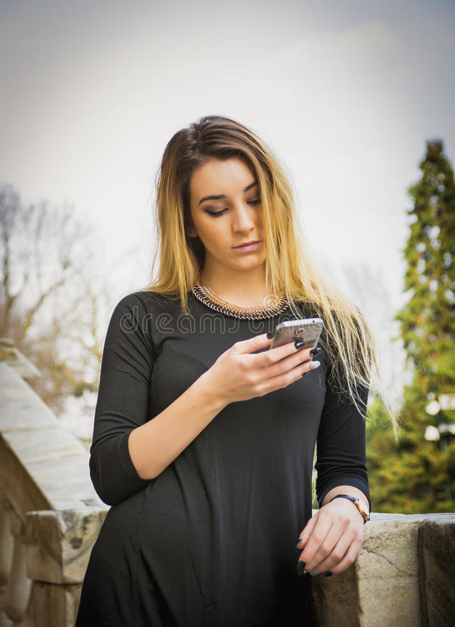 Νέα γυναίκα που χρησιμοποιεί το smartphone στοκ φωτογραφία