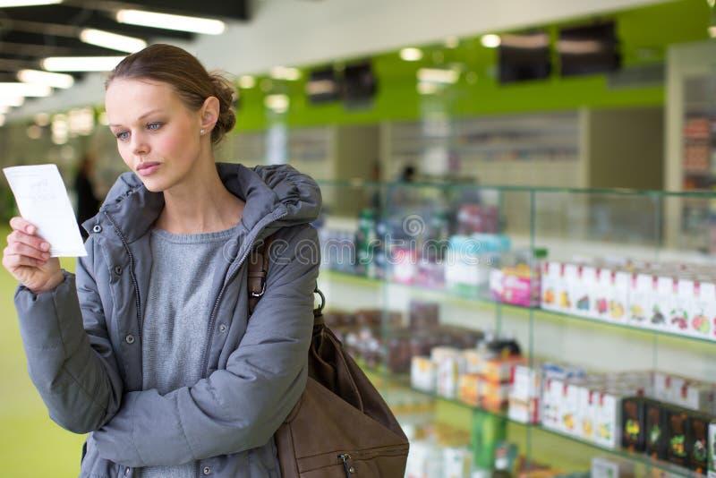 Νέα γυναίκα που ψάχνει τα σωστά χάπια σε ένα σύγχρονο φαρμακείο στοκ εικόνες