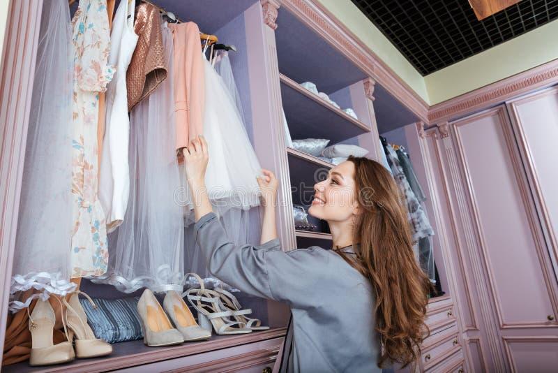 Νέα γυναίκα που ψάχνει τι να φορέσει σε μια ντουλάπα στοκ φωτογραφίες με δικαίωμα ελεύθερης χρήσης