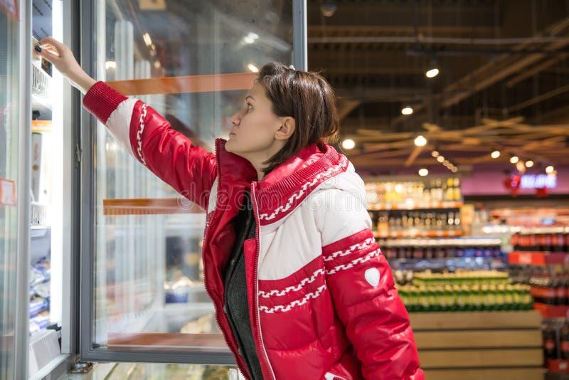 Νέα γυναίκα που ψωνίζει για τα λιωμένα προϊόντα σε ένα μανάβικο Αυτοεξυπηρέτηση στοκ εικόνα