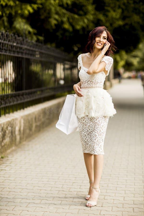 Νέα γυναίκα που ψωνίζει στην οδό στοκ φωτογραφία