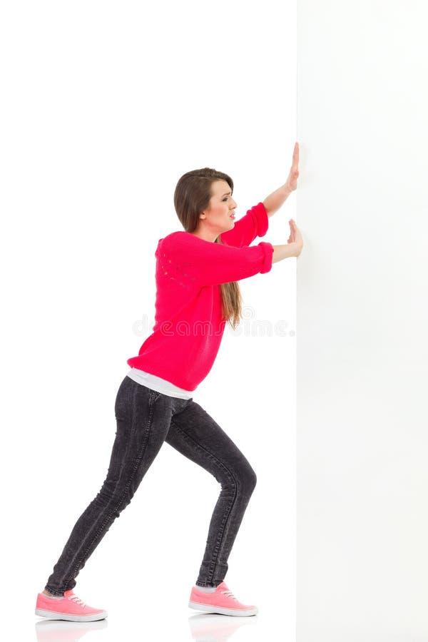 Νέα γυναίκα που ωθεί τον τοίχο στοκ εικόνες