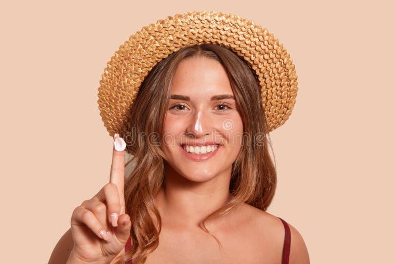 Νέα γυναίκα που sunblock στο πρόσωπό της, και showinig το δάχτυλό της με sunscreen, πρότυπη τοποθέτηση που απομονώνεται πέρα από  στοκ φωτογραφίες