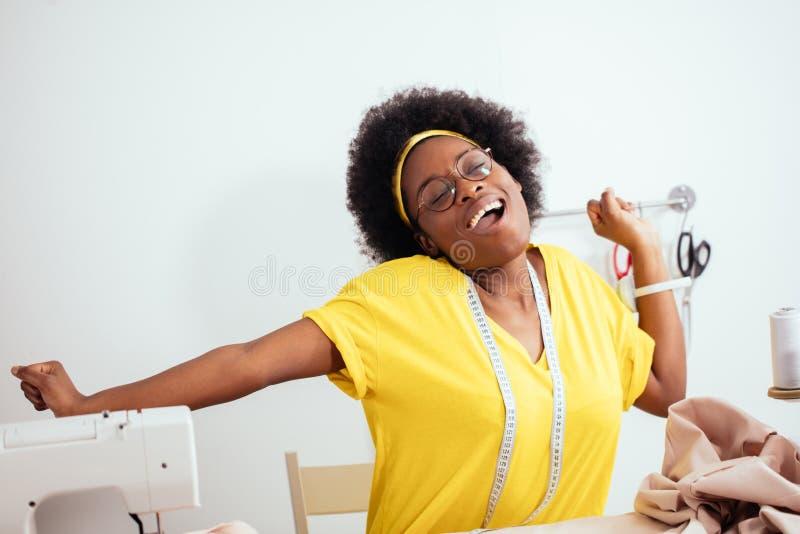Νέα γυναίκα ραφτών που χορεύει με το μανεκέν στην προσαρμογή του εργαστηρίου στοκ εικόνα
