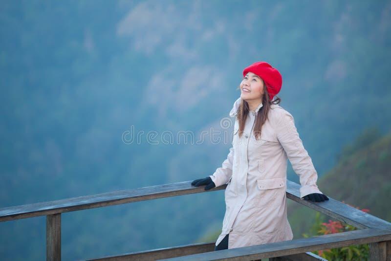 Νέα γυναίκα σε έναν απότομο βράχο που αγνοεί τα βουνά στοκ εικόνα με δικαίωμα ελεύθερης χρήσης