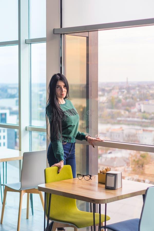 Νέα γυναίκα σε έναν καφέ κοντά στον πίνακα σε αναμονή για να εξετάσει ένα μεγάλο παράθυρο στοκ εικόνα