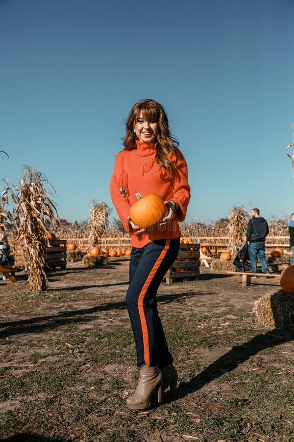 Νέα γυναίκα σε ένα αγρόκτημα κολοκύθας Όμορφο κορίτσι κοντά στις κολοκύθες Ένα κορίτσι με μια κολοκύθα Τομέας κολοκύθας Αγρόκτημα στοκ εικόνες