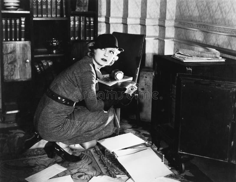 Νέα γυναίκα σε ένα γραφείο δίπλα σε ένα χρηματοκιβώτιο, που κοιτάζει πέρα από τον ώμο της (όλα τα πρόσωπα που απεικονίζονται δεν  στοκ φωτογραφία με δικαίωμα ελεύθερης χρήσης