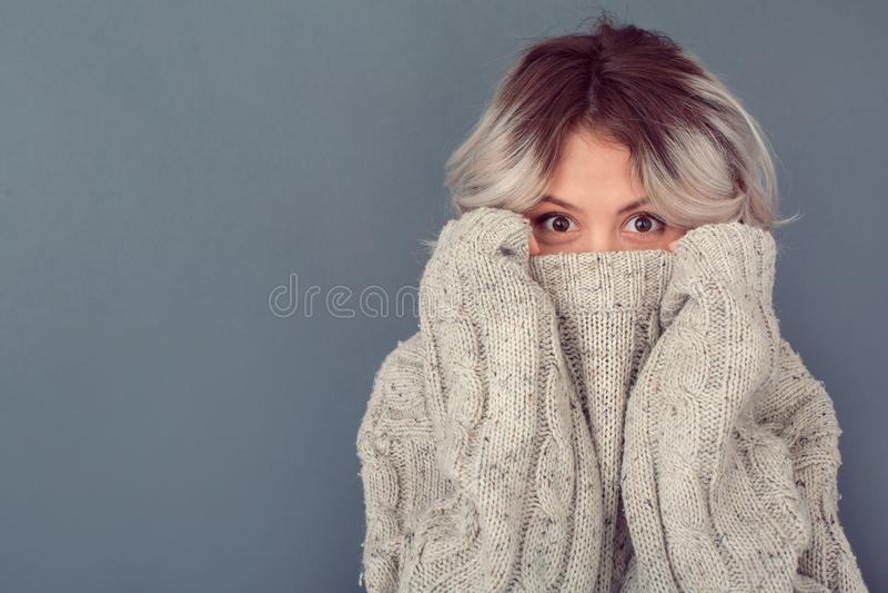 Νέα γυναίκα σε ένα μάλλινο πουλόβερ στο γκρίζο κρύψιμο χειμερινής έννοιας τοίχων στοκ εικόνα με δικαίωμα ελεύθερης χρήσης
