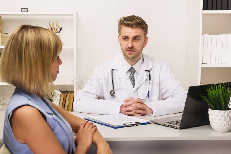 Νέα γυναίκα σε διαβουλεύσεις με έναν αρσενικό χειρούργο ή έναν θεράποντα στο γραφείο του στοκ φωτογραφία με δικαίωμα ελεύθερης χρήσης