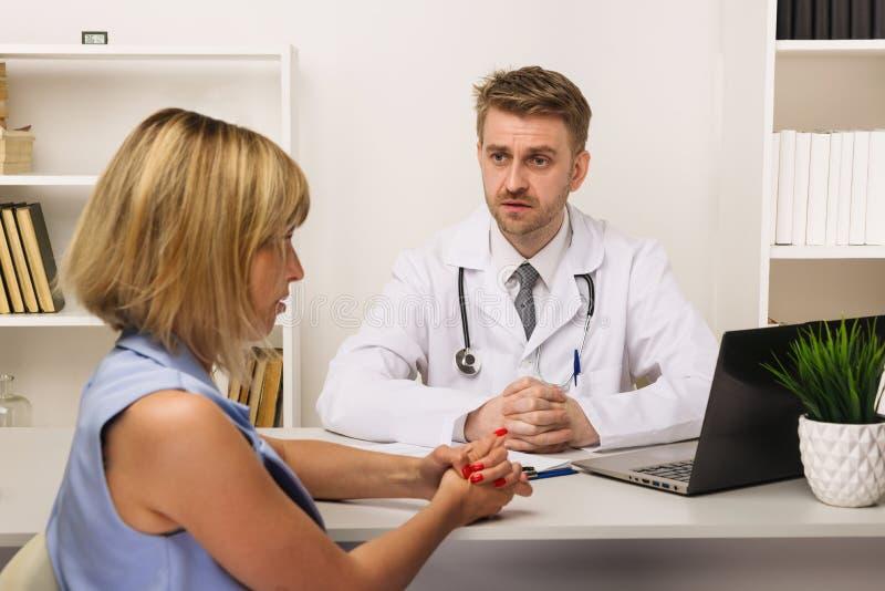 Νέα γυναίκα σε διαβουλεύσεις με έναν αρσενικό χειρούργο ή έναν θεράποντα στο γραφείο του στοκ εικόνα με δικαίωμα ελεύθερης χρήσης