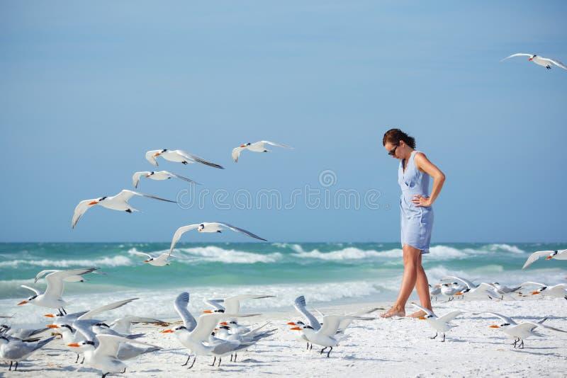 Νέα γυναίκα σε μια παραλία όπου seagulls πετώντας στοκ εικόνες