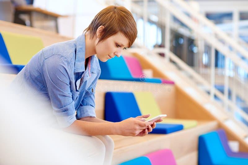 Νέα γυναίκα σπουδαστής που διαβάζει ένα μήνυμα στο κινητό τηλέφωνό της στοκ φωτογραφίες με δικαίωμα ελεύθερης χρήσης