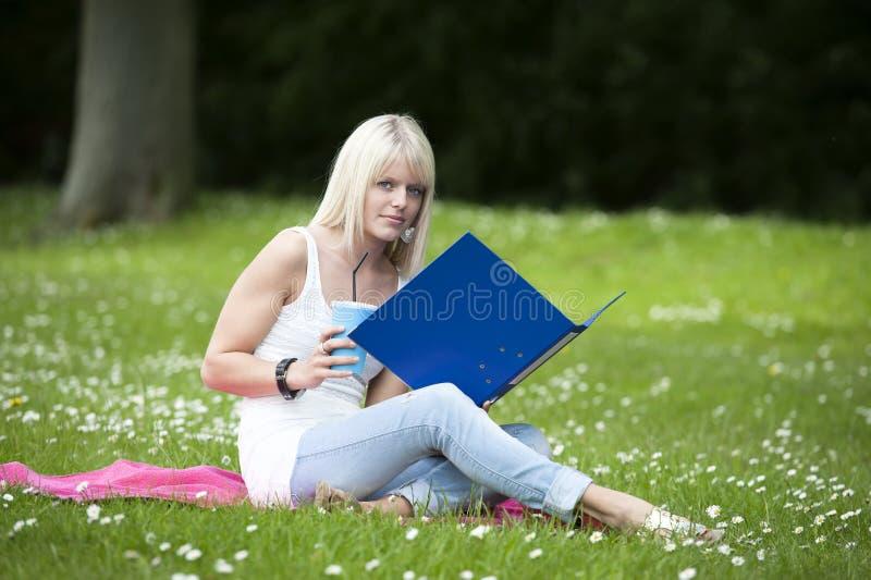 Νέα γυναίκα σπουδαστής στο πάρκο στοκ εικόνες