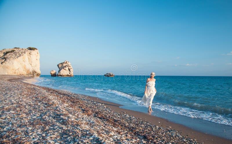 Νέα γυναίκα στα άσπρα sundress που περπατά κατά μήκος της ακτής στοκ εικόνες