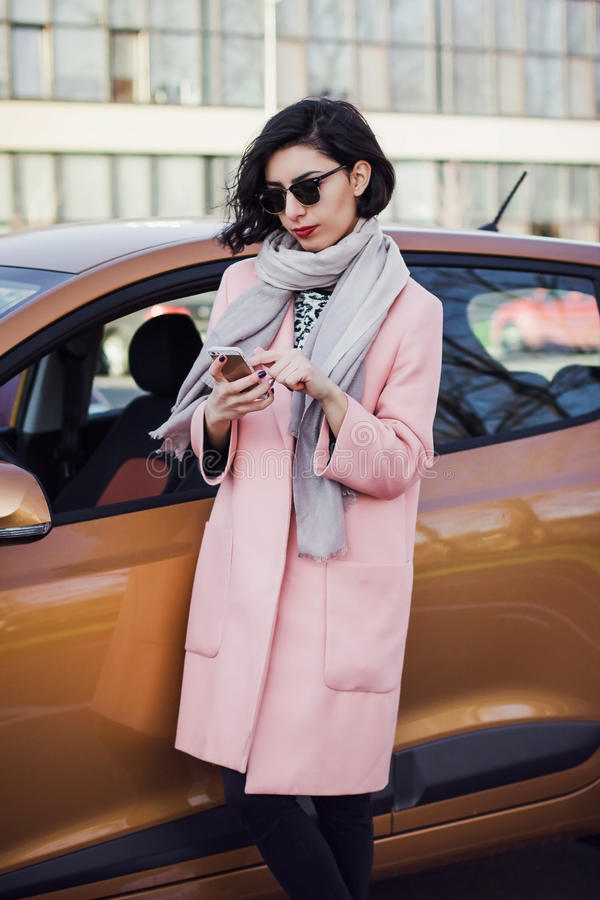 Νέα γυναίκα στα γυαλιά ηλίου με το τηλέφωνο στοκ εικόνες με δικαίωμα ελεύθερης χρήσης