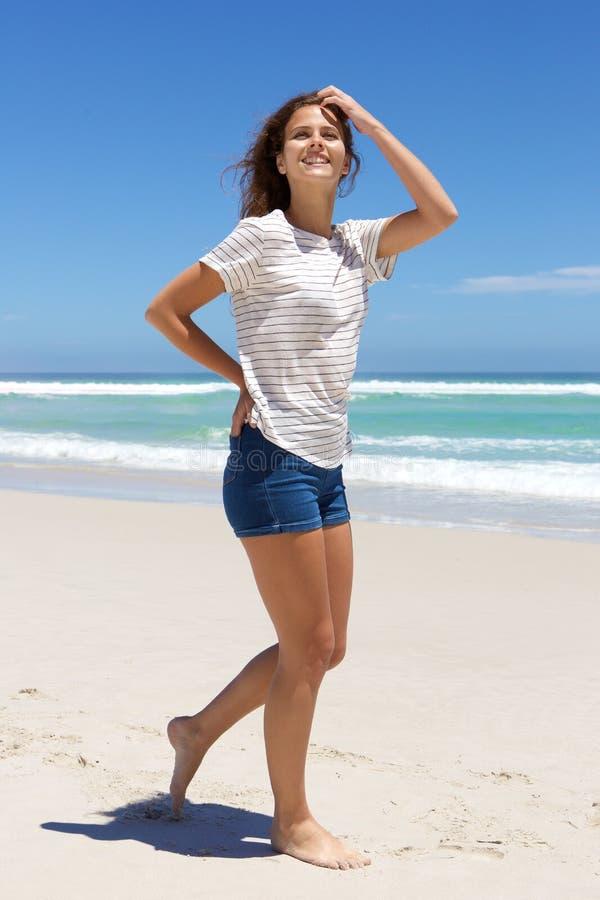 Νέα γυναίκα στα σορτς που περπατά στην παραλία στοκ εικόνα