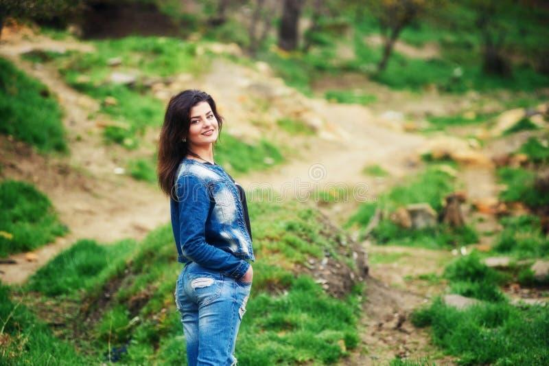 Νέα γυναίκα στα τζιν και σακάκι στο πάρκο στοκ φωτογραφίες με δικαίωμα ελεύθερης χρήσης