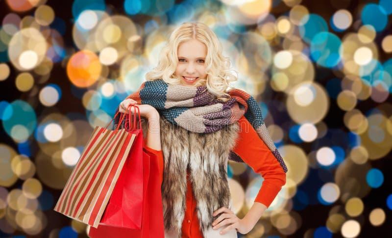 Νέα γυναίκα στα χειμερινά ενδύματα με τις τσάντες αγορών στοκ εικόνα με δικαίωμα ελεύθερης χρήσης