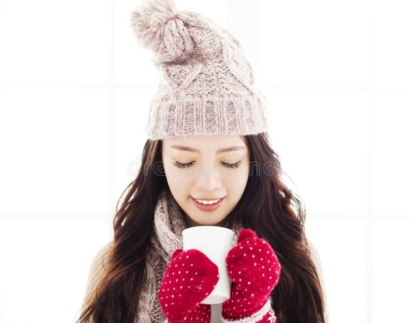 Νέα γυναίκα στα χειμερινά ενδύματα που έχουν το ζεστό ποτό στοκ εικόνα με δικαίωμα ελεύθερης χρήσης