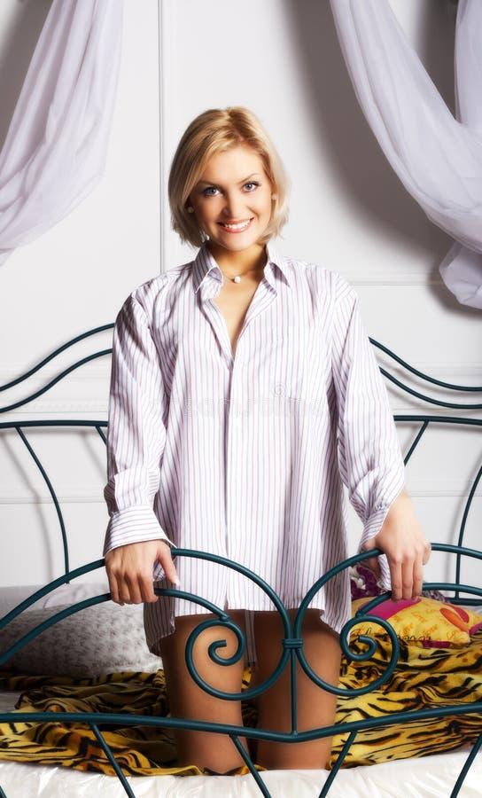 Νέα γυναίκα στην άσπρη τοποθέτηση πουκάμισων στο κρεβάτι στοκ εικόνες