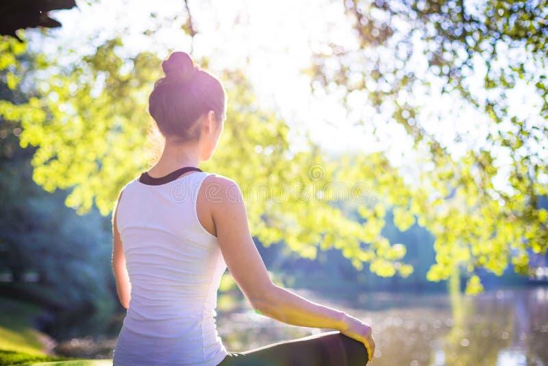 Νέα γυναίκα στην άσπρη τοπ γιόγκα άσκησης στην όμορφη φύση Περισυλλογή στην ηλιόλουστη ημέρα πρωινού στοκ εικόνα