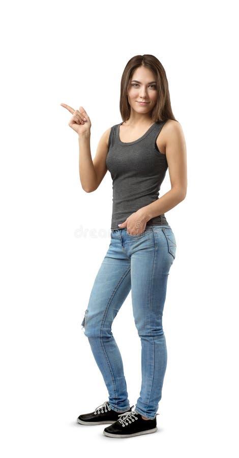 Νέα γυναίκα στην αμάνικη κορυφή και τζιν που στέκονται στην μισό-στροφή με το αριστερό χέρι στην τσέπη και τη δεξιά υπόδειξη side στοκ εικόνες με δικαίωμα ελεύθερης χρήσης