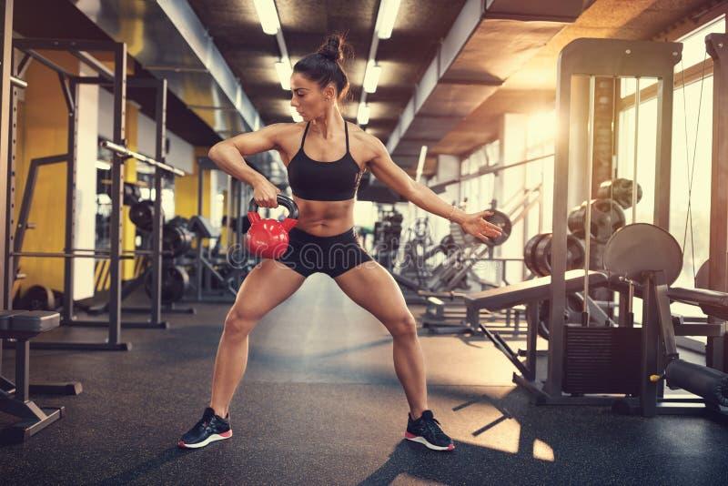 Νέα γυναίκα στην κατάρτιση στη γυμναστική στοκ εικόνες