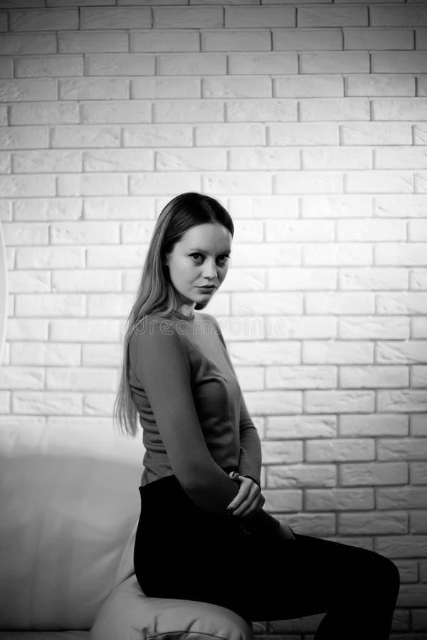 Νέα γυναίκα στην κόκκινη μπλούζα δίπλα στο μοντέρνο νεαρό δικυκλιστή μόδας τουβλότοιχος στοκ φωτογραφία με δικαίωμα ελεύθερης χρήσης