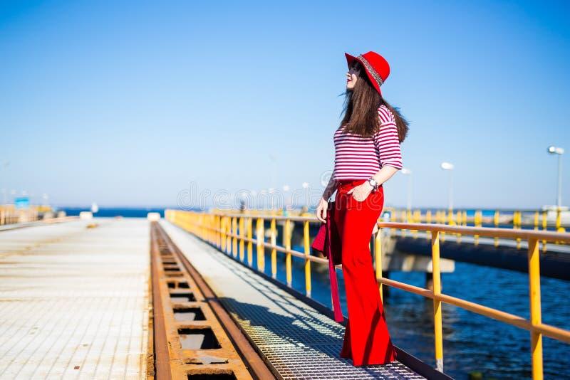 Νέα γυναίκα στην κόκκινη τοποθέτηση στην αποβάθρα στοκ φωτογραφίες