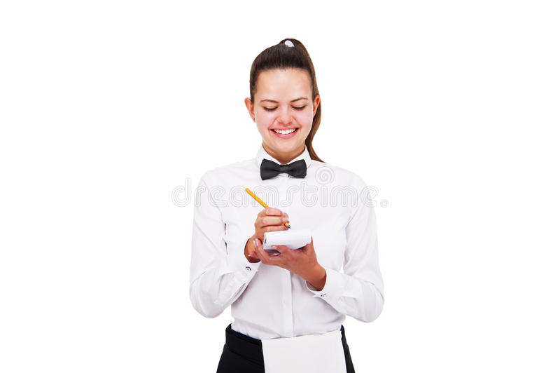 Νέα γυναίκα στην ομοιόμορφη διαταγή γραψίματος σερβιτόρων πέρα από το άσπρο backgroun στοκ εικόνες