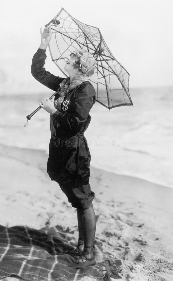 Νέα γυναίκα στην παραλία με μια ομπρέλα που μοιάζει με έναν Ιστό αραχνών (όλα τα πρόσωπα που απεικονίζονται δεν ζουν περισσότερο  στοκ φωτογραφίες με δικαίωμα ελεύθερης χρήσης