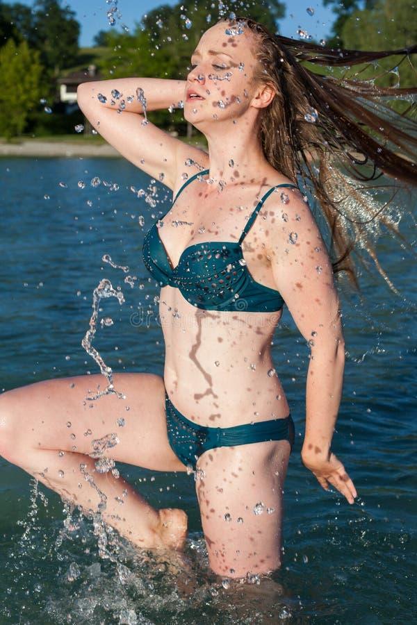 Νέα γυναίκα στη λίμνη που κτυπά την υγρή τρίχα εντυπωσιακά στοκ φωτογραφία