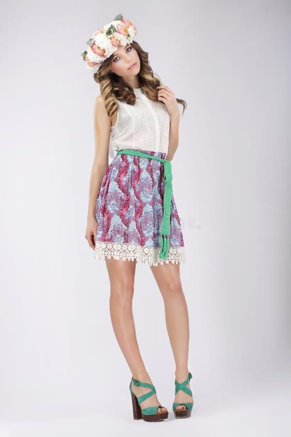 Νέα γυναίκα στη δαντελλωτός φούστα και μπλούζα με τα λουλούδια στοκ εικόνα