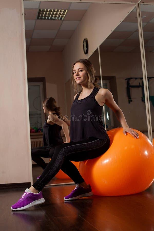 Νέα γυναίκα στη γυμναστική στοκ φωτογραφία