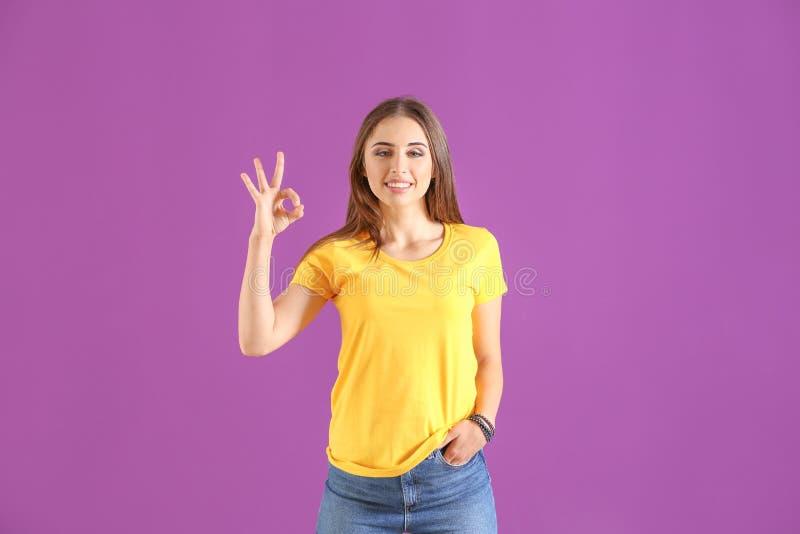 Νέα γυναίκα στη μοντέρνη μπλούζα που παρουσιάζει ΕΝΤΑΞΕΙ χειρονομία στο υπόβαθρο χρώματος στοκ φωτογραφία