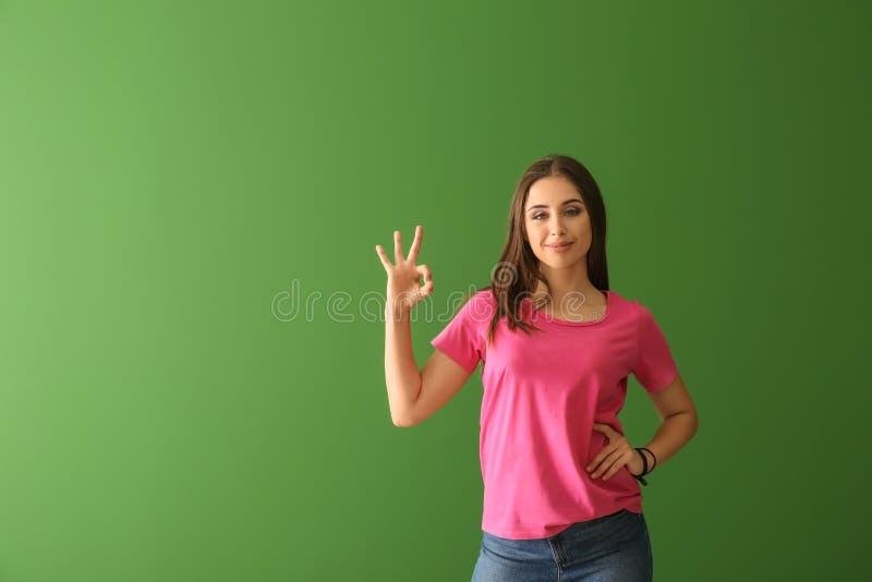 Νέα γυναίκα στη μοντέρνη μπλούζα που παρουσιάζει ΕΝΤΑΞΕΙ χειρονομία στο υπόβαθρο χρώματος στοκ εικόνα με δικαίωμα ελεύθερης χρήσης