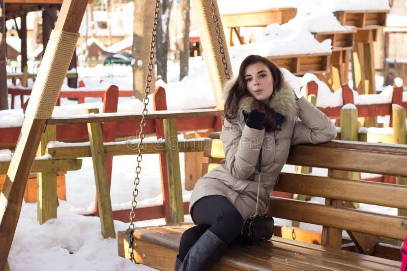Νέα γυναίκα στη συνεδρίαση χειμερινών πάρκων στον πάγκο στοκ φωτογραφίες με δικαίωμα ελεύθερης χρήσης