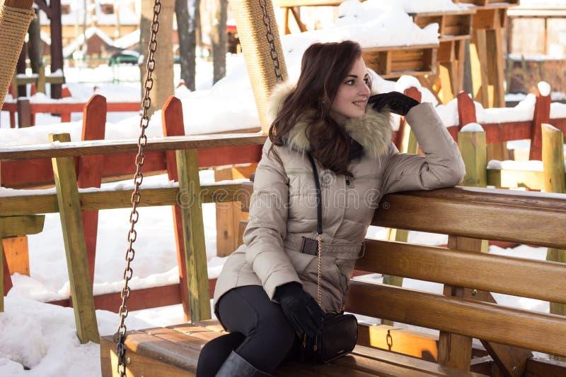 Νέα γυναίκα στη συνεδρίαση χειμερινών πάρκων στον πάγκο στοκ φωτογραφία